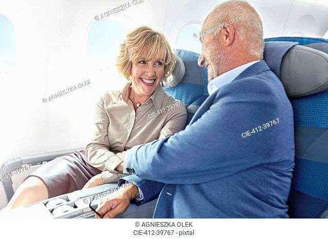 Affectionate mature couple holding hands on airplane