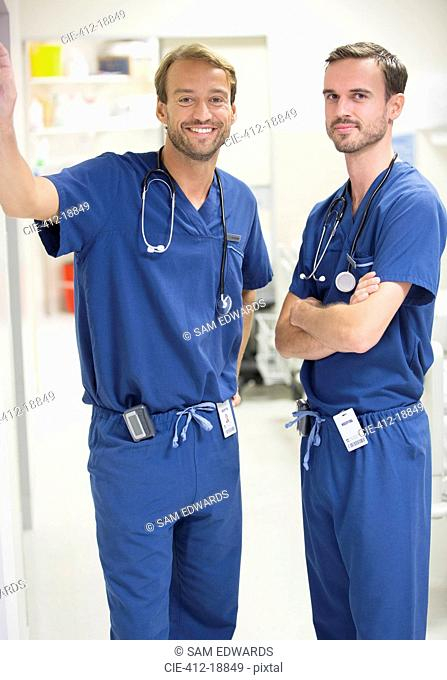 Two smiling male doctors wearing scrubs standing in hospital ward