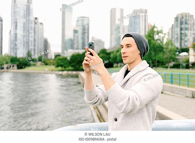 Young man taking photo on seawall, Yaletown, Vancouver, Canada