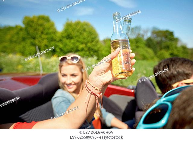 summer holidays, road trip, vacation, travel and people concept - happy young women with fizzy drinks driving in convertible car