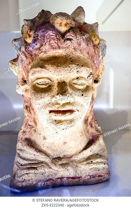 Terracotta antefix in head of a smiling young satyr with a wreath of berries and leaves from the sanctuary of Hercules in the locality of sant'Antonio -...