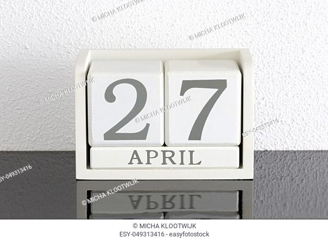 White block calendar present date 27 and month April on white wall background