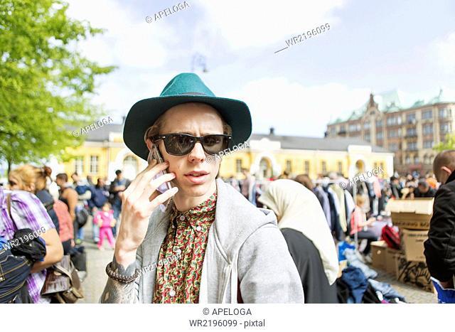 Man wearing sunglasses talking on phone at flea market
