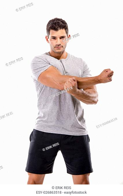 Athletic man doing some warming exercises, isolated over a white background