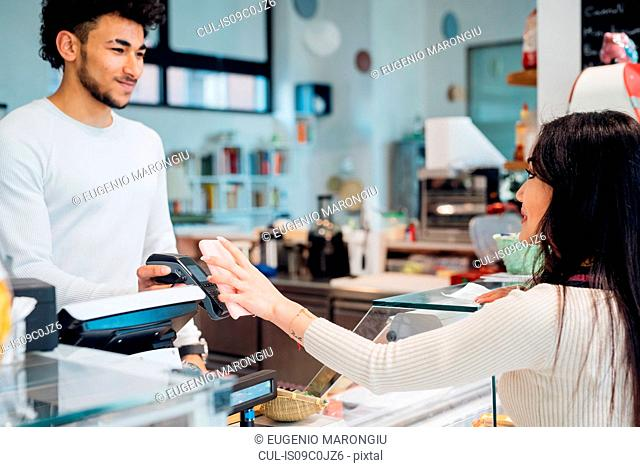 Young businesswoman making smartphone payment at cafe counter