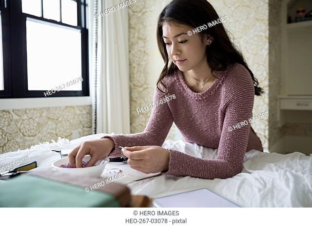 Teenage girl making jewelry
