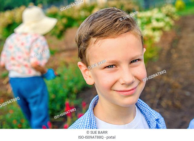 Portrait of boy in front of great grandmother on farm