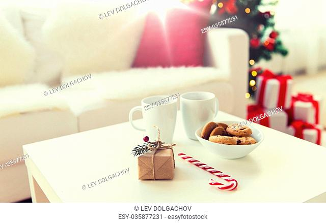christmas, holidays and winter concept - close up of gift, oat cookies, sugar cane candy and cups on table at home