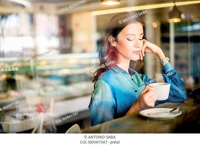 Beautiful woman at cafe window seat, Dubai, United Arab Emirates
