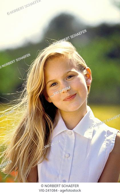 portrait, smiling girl, with long blond hair, 12 years, white sleeveless blouse, sits on a meadow sprinkeled with corn poppies and yellow flowers  - GERMANY