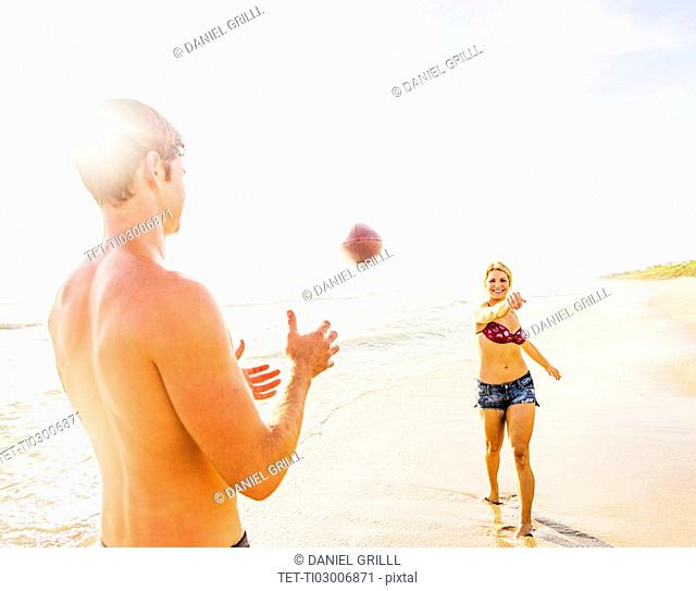 Young couple throwing football on beach