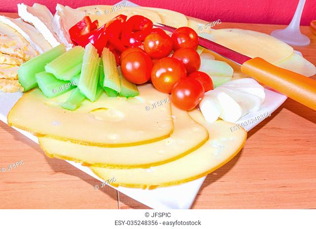 Cheese platter with fruits and vegetables / cheese plate garnished
