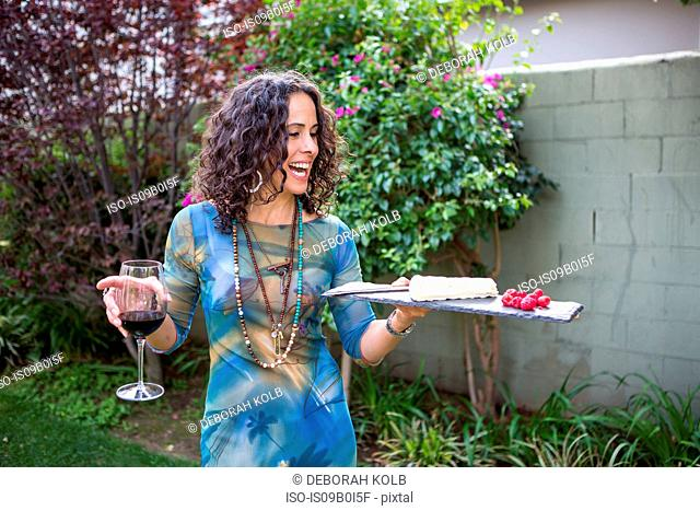 Mature woman holding cutting board and red wine at garden party