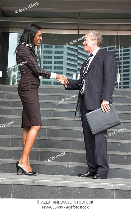 Business people shaking hands outside offices