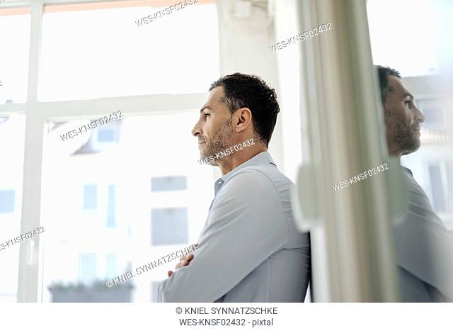 Businessman in office leaning against wall at the window