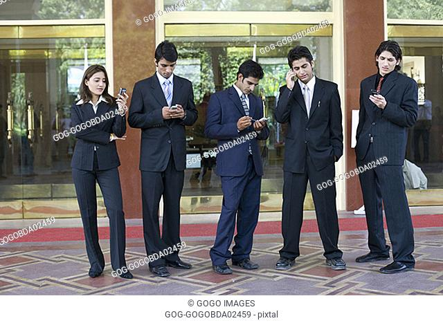 Businesspeople using cell phones and electronic organizers