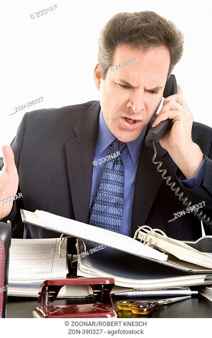 Geschäftsmann am Schreibtisch hat Akten vor sich liegen und telefoniert verärgert