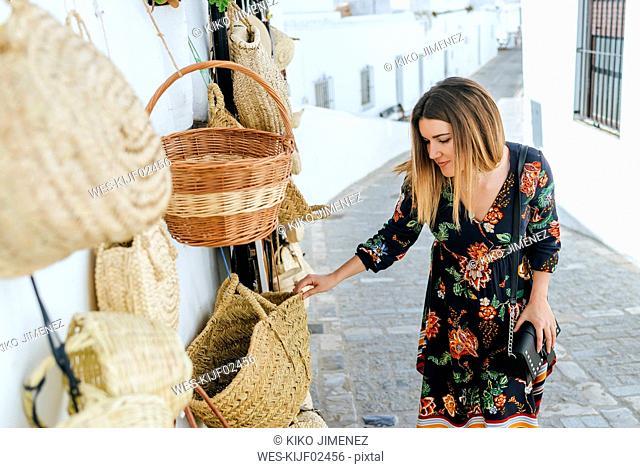 Spain, Cadiz, Vejer de la Frontera, fashionable woman looking at bags and baskets at a shop