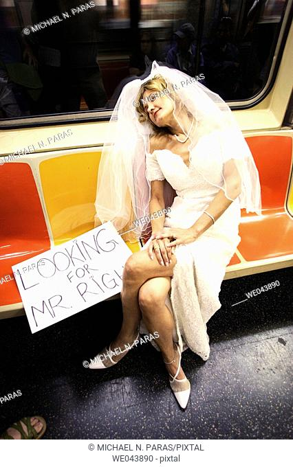 Bride asleep on nyc subway with 'Looking Mr. Right' sign by her side