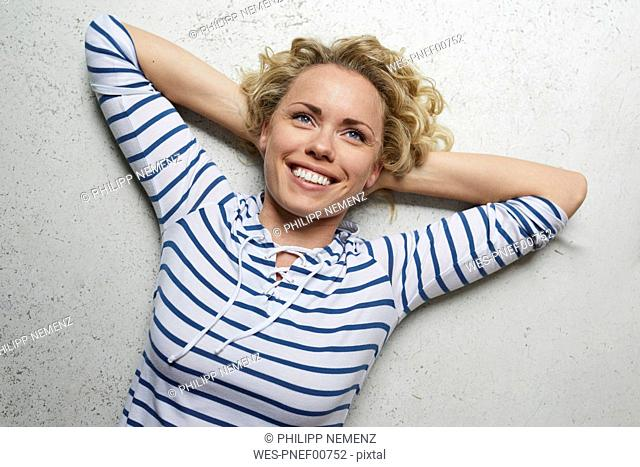 Portrait of happy woman with hands behind head