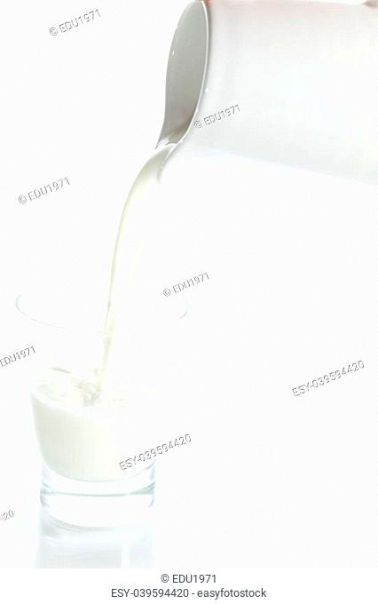 Filling a glass of milk with a porcelain jar