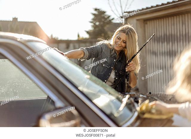 Mature woman and girl cleaning car together
