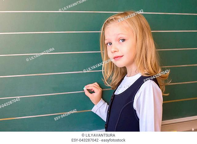 a small beauty of a first grade student at a school near the board solves the problem. emotions of schoolgirls