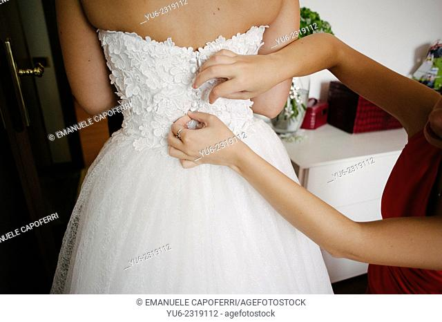 A friend helps the bride to dress