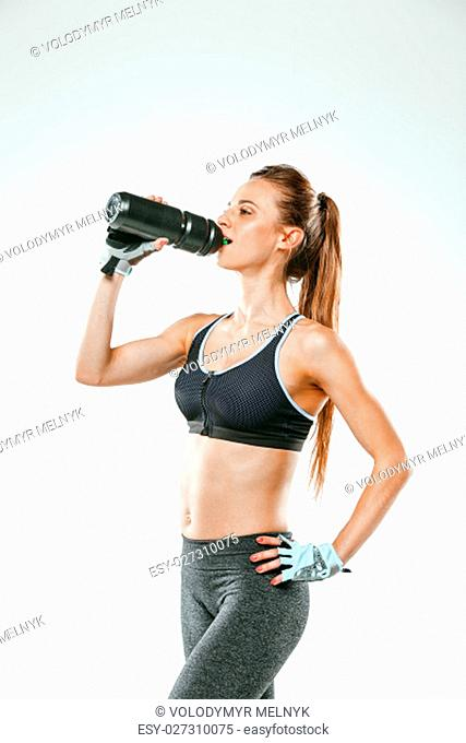 Muscular young woman athlete drinking water on black background