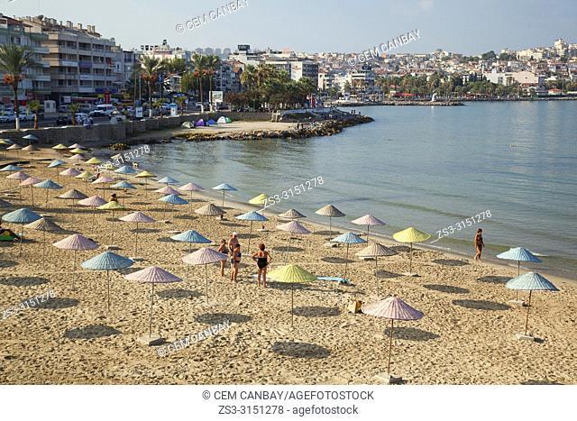 Tourists and locals at the sandy beach near the port, Kusadasi, Izmir Province, Turkey, Europe