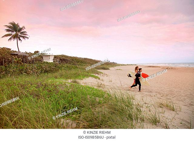 Male lifeguard and surfer running toward sea from beach