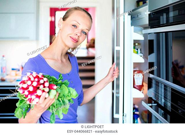 Pretty, young woman taking fresh vegetables from her fridge - being on a gluten free vegan diet does not seem to be a problem for her (shallow DOF; color toned...
