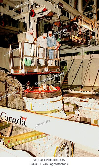 10/03/1998 --- As the bucket operator left lowers them into the open payload bay of the orbiter Endeavour, STS-88 Mission Specialists Jerry L