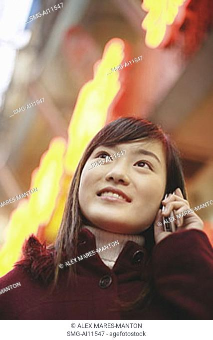 Young woman using mobile phone, looking up