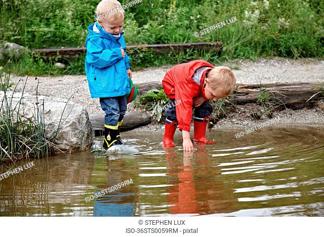 Toddler boys playing in creek