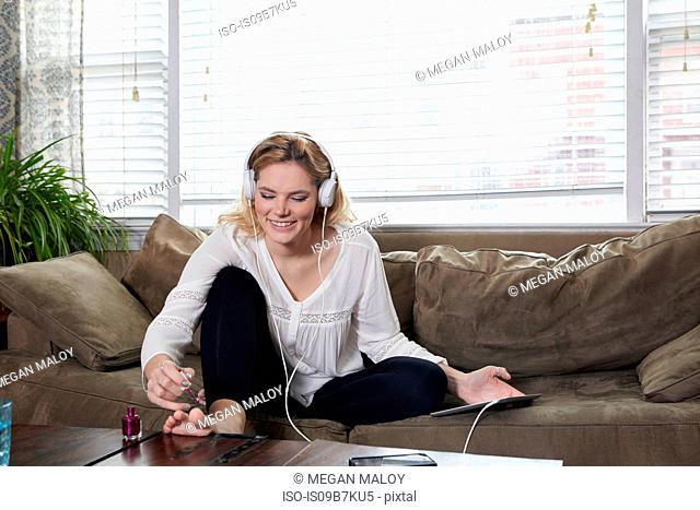 Woman painting nails and listening to music on sofa