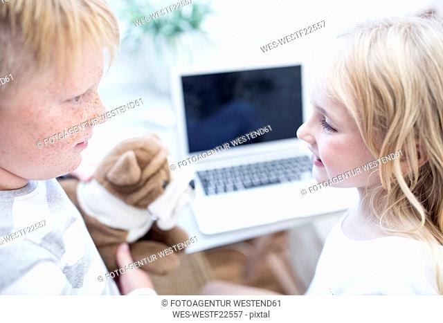 Brother and sister with cuddly toy looking at each other in front of laptop