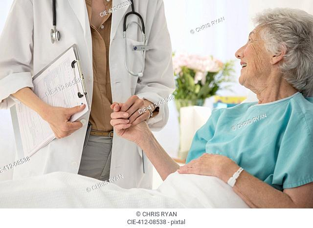 Doctor and aging patient holding hands in hospital