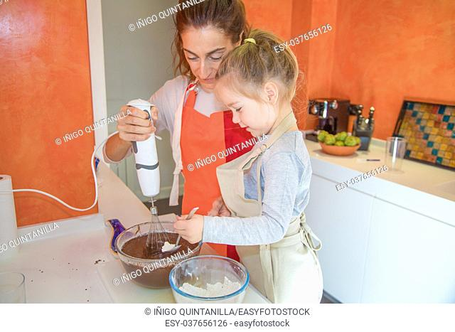 four years old girl pouring flour on chocolate cream and woman whisking with electric mixer in glass bowl, in teamwork, cooking a sponge cake at kitchen home