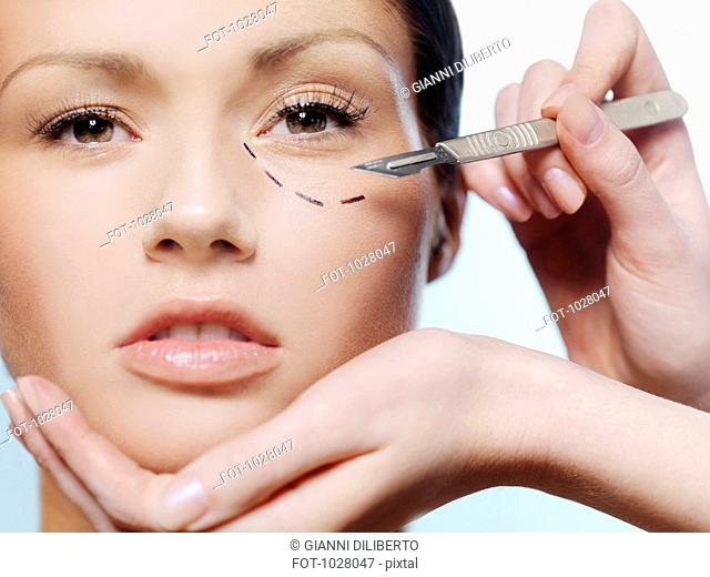 Hands holding a scalpel and a woman's face with a dotted line under her eye