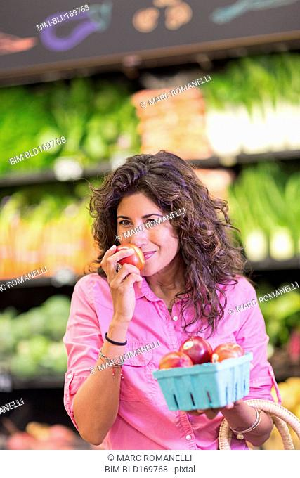 Hispanic woman checking produce at grocery store