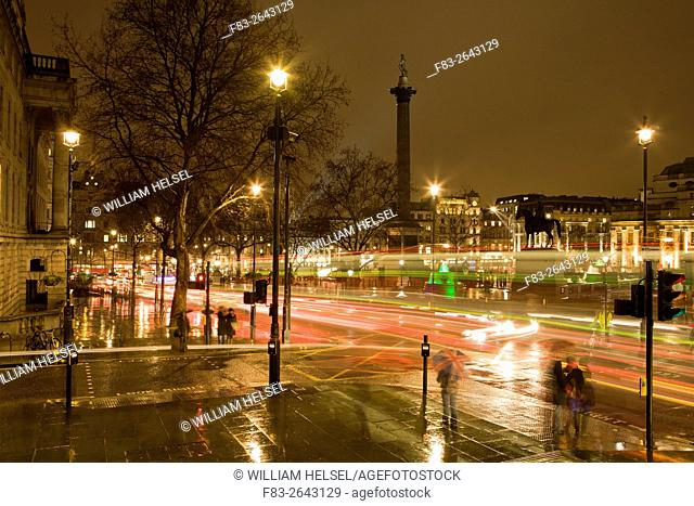 London, England, Trafalgar Square at night in rain with double-deck busses, people with umbrellas