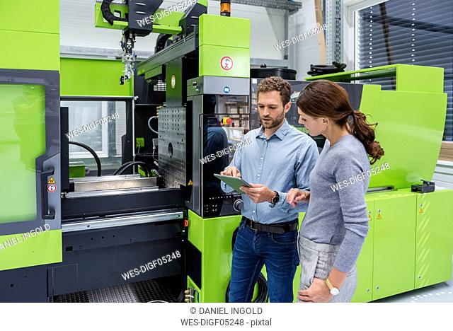 Colleagues in high tech company controlling manufacturing machines, using digital tablet