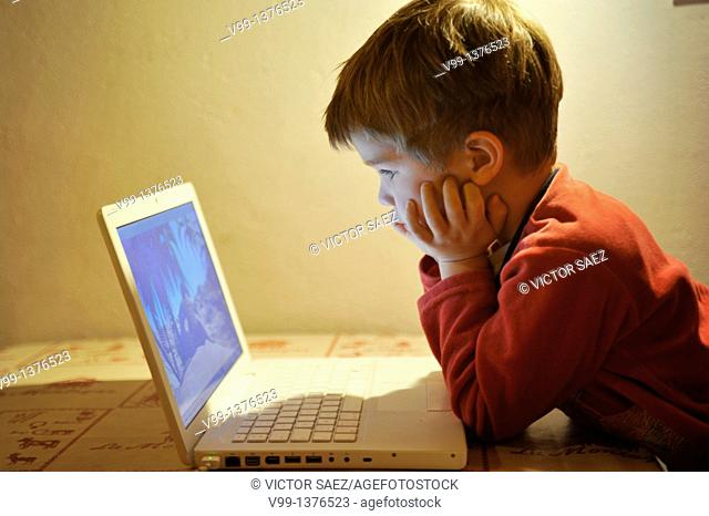 young boy who watches a movie on the computer
