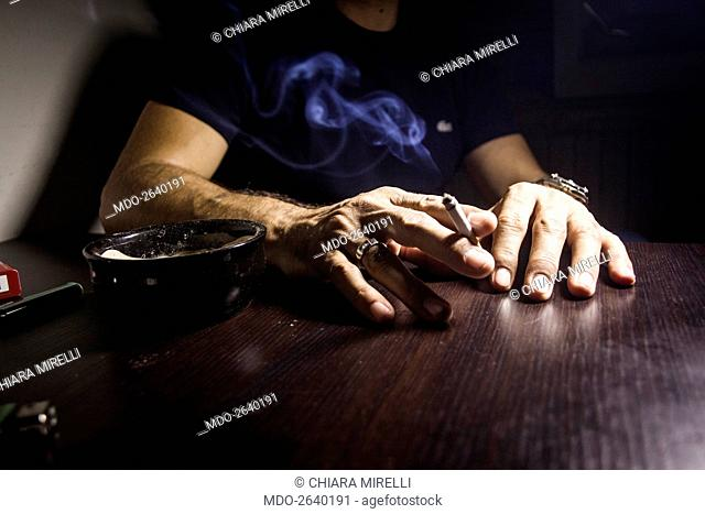 Close-up of hands resting on a table and with a cigarette between the fingers. Brescia (Italy), 7th September 2014