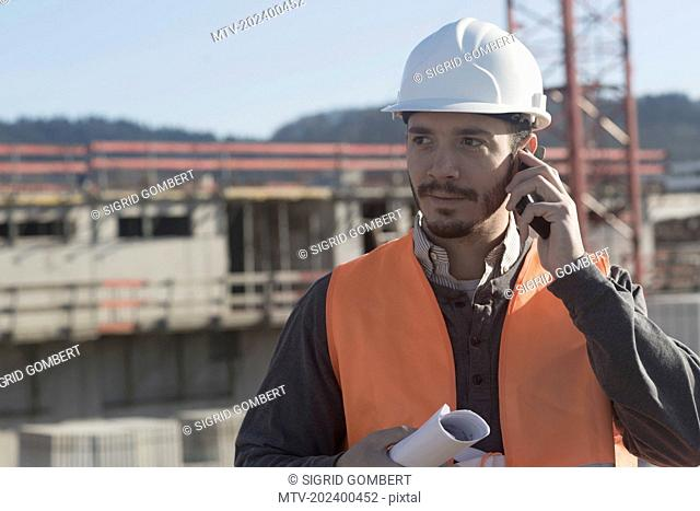Young male engineer holding blueprint and talking on a mobile phone at construction site, Freiburg Im Breisgau, Baden-Württemberg, Germany