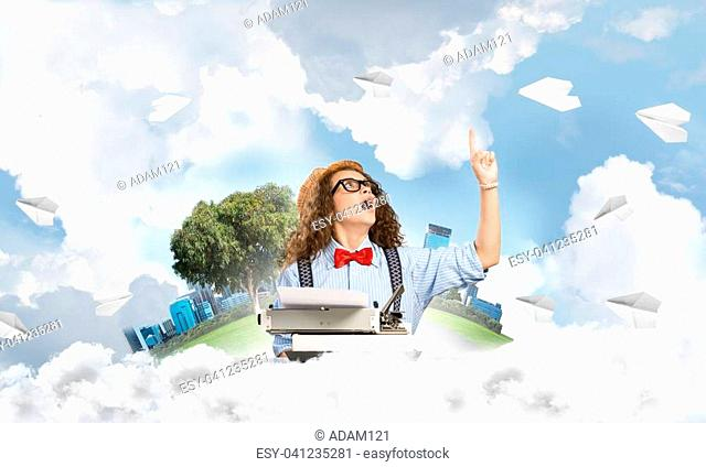 Young woman writer in hat and eyeglasses using typing machine and pointing upside while sitting at the table among flying paper planes with floating city island...