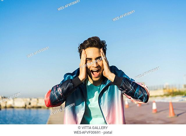 Surprised man screaming for joy with hands on head