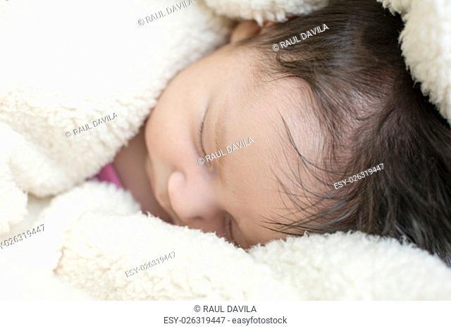 little newborn girl sleeping on its side on a blanket of fluffy white