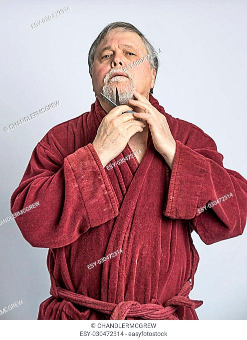 Senior gray haired man wearing heavy maroon robe trimming his beard and mustache with scissors
